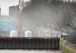 © Licensed to London News Pictures. 14/12/2019. London, UK. Smoke is seen rising from the Thames Tideway sewer works building site on The River Thames at Chelsea Embankment after a controlled explosion was carried out on a WW2 unexploded bomb. Photo credit: Peter Macdiarmid/LNP