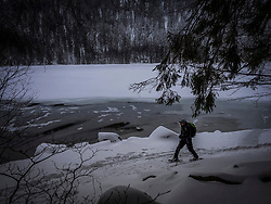 Man hiking with snowshoes on the shore of lake Feldsee, Black forest, Baden-Wuerttemberg, Germany