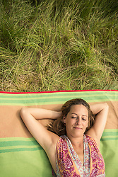 Directly above shot of woman resting on picnic blanket on meadow, Bavaria, Germany