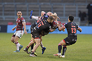 Joe Bullock (10) of Wigan Warriors is tackled by Ryan Lannon (11) of Salford Red Devils and Jack Wells (26) of Salford Red Devils