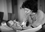 Hebamme mit Neugeborenem; sage-femme avec nouveau-né, 2004. Midwife with newborn baby. © Romano P. Riedo