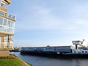 Containervervoer met binnenvaartschip over rivier de Hollandse IJssel - Transport of freight container with a barge over a Dutch river called de Hollandse IJssel