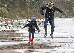 © Licensed to London News Pictures. 08/02/2021. Surrey, UK. Father and son break some ice on top of Box Hill in Surrey this morning as Storm Darcy hits the South East with more snow and freezing temperatures today. The Met Office have issue numerous weather warnings for heavy snow and ice with disruption to travel, power cuts and possible stranded vehicles as the bad weather continues.  Photo credit: Alex Lentati/LNP