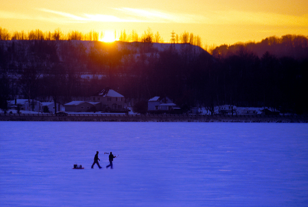 A PAIR OF ICE FISHERMEN CARRY AND AUGER AND PULL A SLED AS THEY WALK ACROSS FROZEN TEAL LAKE IN NEGAUNEE MICHIGAN AT DUSK.