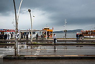 A woman crosses the street on a rainy afternoon in the port of Ayvalik, Turkey