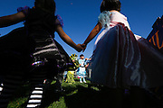 Children hold hands and dance during a Jump For Joy Music performance during the annual Sunnyhills Neighborhood Association's Sunnyhills Pre-Halloween Party at Albert Augustine Jr. Memorial Park in Milpitas, California, on October 26, 2013. (Stan Olszewski/SOSKIphoto)
