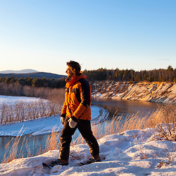 A man snowshoeing on a bluff overlooking the Merrimack River in Canterbury, New Hampshire.