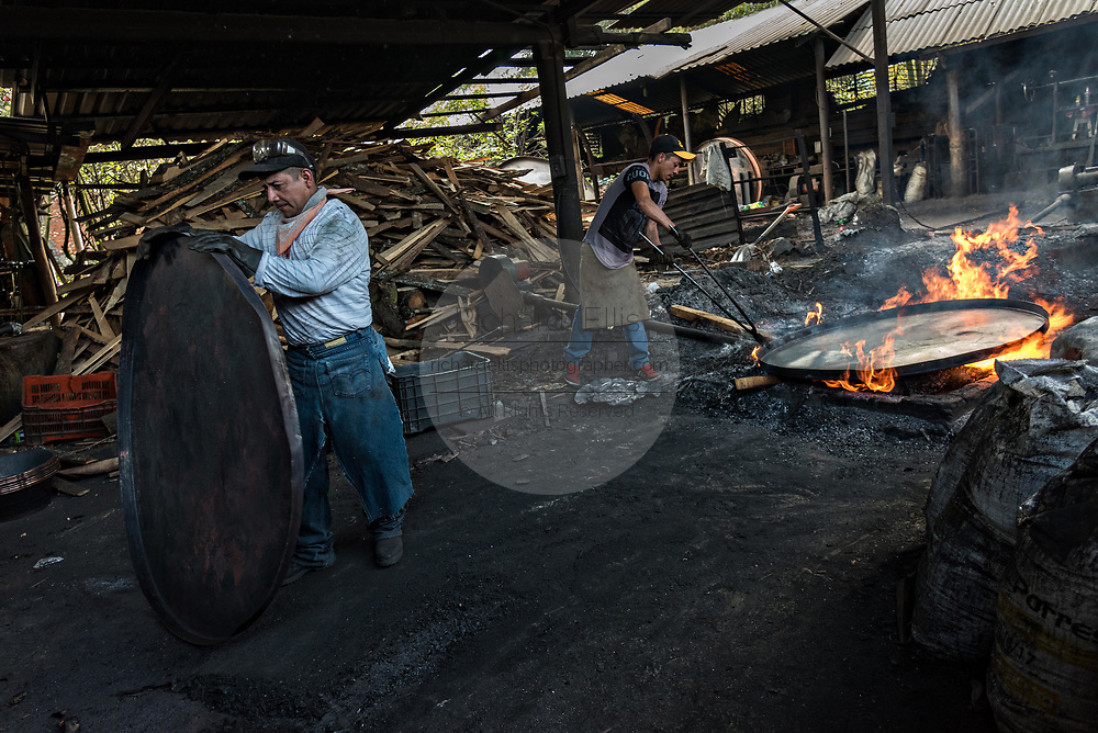 Indigenous Purepecha workers work copper pans on an open forge to begin the process of hardening and forming the pan at a copper workshop in Santa Clara del Cobre, Michoacan, Mexico. The Purepecha people have been crafting copper crafts since the 12th century.