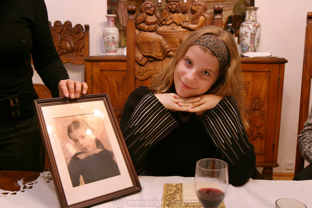 Olga Ledochowicz at her grandmother's apartment in Lodz for All Saints Day dinner. .Photo in frame is her several years before. Lodz, Poland.