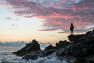 A young woman watches the end of another day unfold in Mexico's Oaxaca State, the sun setting as she stands above the Pacific Ocean on a rocky outcropping.