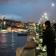 Fishermen line the edge of Galata Bridge with their lines over the side into the Golden Horn. Spanning the Golden Horn and linking Eminonu with Karakoy, the Galata Bridge is a dual-level bridge that handles road, tram, and pedestrian traffic on the top level with restaurants and bars on the level below. In the distance is Galata Tower.