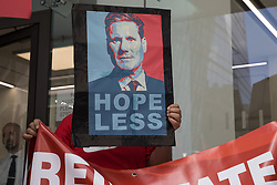 London, UK. 20th July, 2021. A man holds a sign bearing an image of Labour Party leader Sir Keir Starmer at a protest lobby outside the party's headquarters by supporters of left-wing groups. The lobby was organised to coincide with a Labour Party National Executive Committee meeting during which it was asked to proscribe four organisations, Resist, Labour Against the Witchhunt, Labour In Exile and Socialist Appeal, members of which could then be automatically expelled from the Labour Party.
