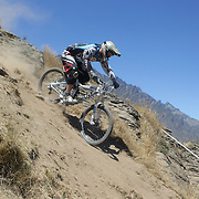 Ant Jackson from Dunedin in action during the New Zealand South Island Downhill Cup Mountain Bike series held on The Remarkables face with a stunning backdrop of the Wakatipu Basin. 150 riders took part in the two day event. Queenstown, Otago, New Zealand. 9th January 2012. Photo Tim Clayton