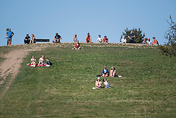 © Licensed to London News Pictures. 14/09/2020. London, UK. Members of the public are seen relaxing in the warm weather on Primrose Hill in North London as the UK Experiences a mini heatwave. New Coronavirus restrictions introduced today prevent people from gathering in groups of more than six. Photo credit: Ben Cawthra/LNP