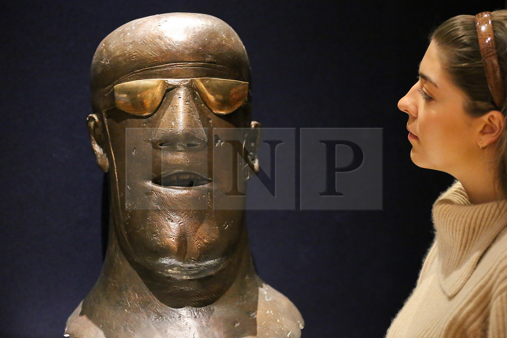 "© Licensed to London News Pictures. 12/11/2018. London, UK. A member of staff looks at ""Head"", conceived in 1967 by Dame Elisabeth Frink R.A. (British, 1930-1993) signed and numbered 'Frink 3/6' (at the base of the neck)<br /> bronze with a brown patina and polished goggles - (Estimate £100,000-150,000).<br /> <br /> Bonhams Modern British and Irish Art photocall. Auction to be held on 14 November 2018. Photo credit: Dinendra Haria/LNP"