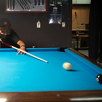 Treyshawn Bia, 13, practices pool Tuesday evening at Q & A Billiards in Gallup. He is learning competitive billiards from Gina Kim, the owner of Q&A Billiards.