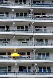 Solitary yellow parasol on balcony of high rise apartment building in Mitte Berlin Germany