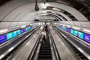 A woman wearing a face mask comes down a nearly desrted escalator at Bank Station in what would normally be the morning rush hour in the City of London on March 17th, 2020. The financial district of the UK is unusually quiet after the government requested people to refrain from all but essential travel and activities yesterday.