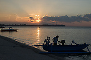 Mount Agung, an active volcano on Bali, seen in the distance at sunset from Gili Meno Island, close to Lombok in Indonesia.<br /> Photo fishermen, boats and tourists on the beach at Gili Meno.