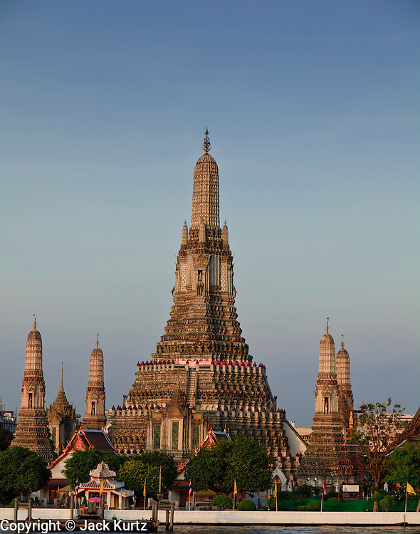 """08 MARCH 2009 -- BANGKOK, THAILAND: Sunrise on Wat Arun, a Buddhist temple (wat) in the Bangkok Yai district of Bangkok, Thailand, on the west bank of the Chao Phraya River. The full name of the temple is Wat Arunratchawararam Ratchaworamahavihara. The outstanding feature of Wat Arun is its central prang (Khmer-style tower). It may be named """"Temple of the Dawn"""" because the first light of morning reflects off the surface of the temple with a pearly iridescence. Steep steps lead to the two terraces. The height is reported by different sources as between 66,80 m and 86 m. The corners are surrounded by 4 smaller satellite prangs. The prangs are decorated by seashells and bits of porcelain which had previously been used as ballast by boats coming to Bangkok from China. The central prang is topped with a seven-pronged trident, referred to by many sources as the """"trident of Shiva"""". Around the base of the prangs are various figures of ancient Chinese soldiers and animals. Over the second terrace are four statues of the Hindu god Indra riding on Erawan. The temple was built in the days of Thailand's ancient capital of Ayutthaya and originally known as Wat Makok (The Olive Temple). In the ensuing era when Thonburi was capital, King Taksin changed the name to Wat Chaeng. The later King Rama II. changed the name to Wat Arunratchatharam. He restored the temple and enlarged the central prang. The work was finished by King Rama III. King Rama IV gave the temple the present name Wat Arunratchawararam. As a sign of changing times, Wat Arun officially ordained its first westerner, an American, in 2005. The central prang symbolizes Mount Meru of the Indian cosmology. The satellite prangs are devoted to the wind god Phra Phai.  Photo By Jack Kurtz"""
