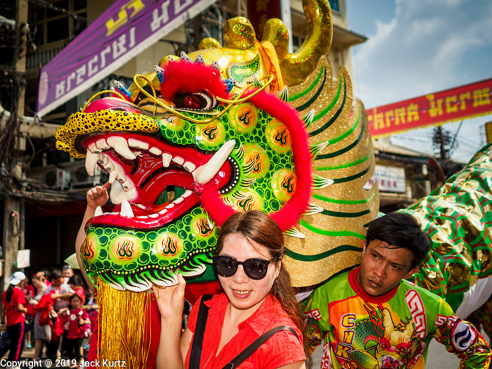 05 FEBRUARY 2019 - BANGKOK, THAILAND: A tourist poses for photos with a Dragon Dance team on Yaowarat Road in Bangkok during Chinese New Year celebrations. Chinese New Year celebrations in Bangkok started on February 4, 2019, although the city's official celebration is February 5 - 6. The coming year will be the Year of the Pig in the Chinese zodiac. About 14% of Thais are of Chinese ancestry and Lunar New Year, also called Chinese New Year or Tet is widely celebrated in Chinese communities in Thailand.     PHOTO BY JACK KURTZ