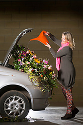 © Licensed to London News Pictures. 20/03/2017. Harrogate, UK. Fiona Fisk water's the flowers in the first of the Floral Bonnets car's to arrive at the Yorkshire Show ground for the Harrogate Flower Show. Floral Bonnets is part of the show's spring theme & has seen Floristry students from across Yorkshire challenged to create a floral display using real cars. The Harrogate Flower Show is the UK's largest exhibition of floral art & this years spring theme HortCouture will see a series of new features celebrating style trends in the home, garden & wardrobe. Photo credit: Andrew McCaren/LNP