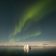 Aurora borealis also known as northern lights, over iceberg. Life in and around the small Inuit settlement of Isortoq (population of 64), in East Greenland.