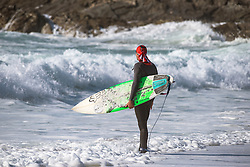 A surfer stands on the shore at Fistral in Newquay, Cornwall.