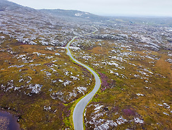 Aerial view from drone of narrow road and rocky landscape on The Bays on East coast of Isle of Harris, Outer Hebrides, Scotland, UK