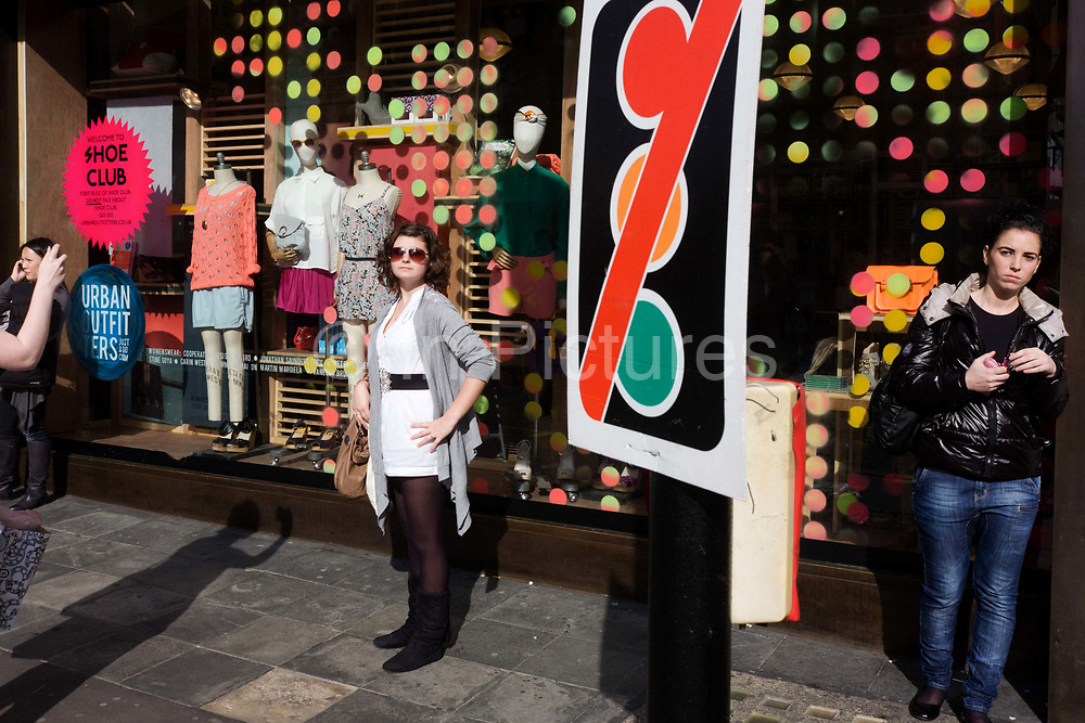 A young woman poses for a friend's camera outside the spotted shop window of Urban Outfitters in Oxford Street, central London, England. To contrast the spotty theme in the window we see instead a sign looming large in the scene that tells drivers on the road that the traffic lights on this junction are inoperative - but they also seem to tell us that spots are forbidden, disallowed in this urban landscape.