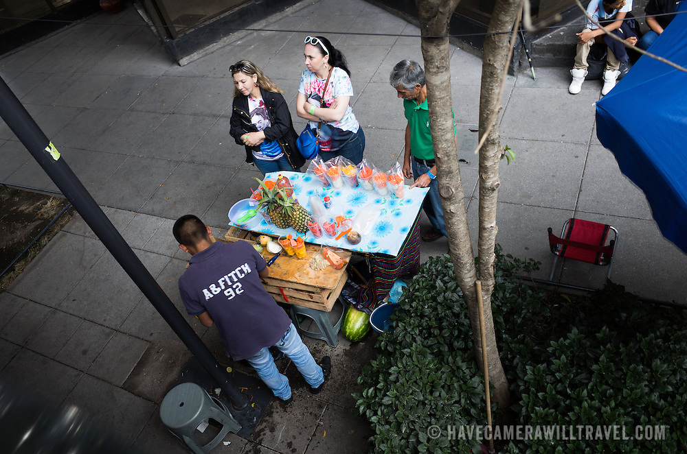 A street vendor sells fresh fruit salad on the side of the street in Mexico City, Mexico.