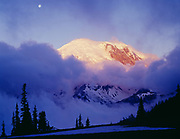 Breaking storm at sunrise revealing full moon and illuminated summit of Mount Rainier, Yakima Park near Sunrise, Mount Rainier National Park, Washington.