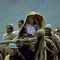 Kashmiri porters carry a wealthy Hindu woman in a sedan chair during a 5-day Himalayan pilgrimage to worship Shiva at Amarnath Cave.