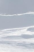 Two climbers walking along a ridge near the summit of active volcano Mount Ruapehu, New Zealand.