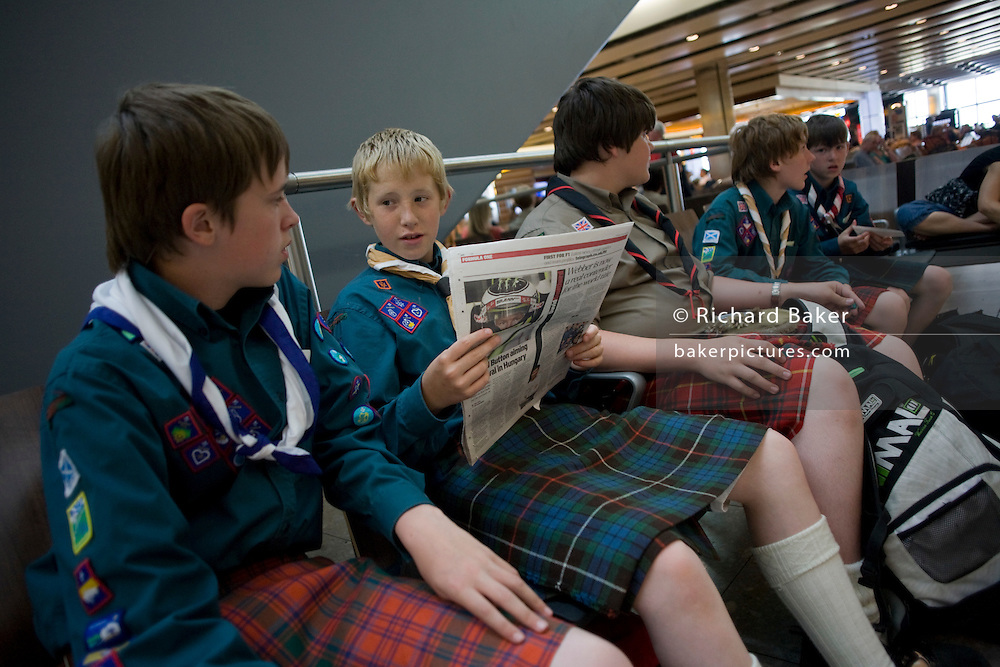 "Boys from a Scottish scout group sit and in the departures concourse of Heathrow Airport's Terminal 5. All wearing traditional kilts favoured by the Scots, the lads are en-route between Switzerland and Scotland after a week's international jamboree in the Alps. Their sleeves are filled with the stitched badges of past achievements and one reads a newspaper while the others pass away the time before their flight by watching other passengers. The kilt's are alternately red and green and historically, relate to their wearers old family clans. From writer Alain de Botton's book project ""A Week at the Airport: A Heathrow Diary"" (2009)."