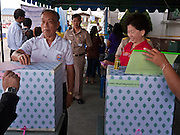 03 JULY 2011 - SAMUT PRAKAN, THAILAND:  The first voter drops his ballot into the ballot box in Samut Prakan, Thailand, Sunday, July 3. He later told a reporter from Thai television that he voted for Pheu Thai. More than 47,000,000 Thais were registered to vote in Sunday's election, which had turned into a referendum on the current government, led, by the Thai Democrats and the oppositionPheu Thai party. Pheu Thai is the latest political incarnation of ousted Thai Prime Minister Thaksin Shinawatra. PT is led by his youngest sister, Yingluck Shinawatra, who is the party's candidate for Prime Minister. Exit polling by three Thai polling firms showed Pheu Thai winning a landslide election.       PHOTO BY JACK KURTZ