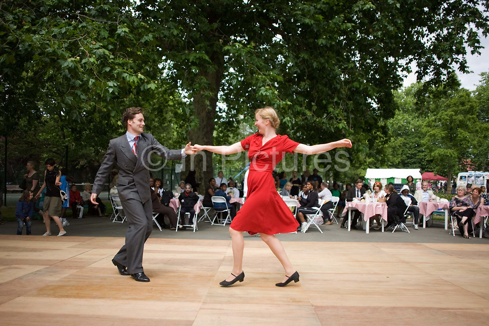A young couple demonstrate their rock 'n' roll dancing skills in front of a crowd in Myatts Fields park in Camberwell, South London UK. Spinning his partner on the specially-laid flooring, the gentleman is dressed in a double-breasted suit in keeping with the 1950s theme of this fair's celebration of a newly-refurbished park. The lady wears a red dress and holds her arm out to regain balance as she is pulled back towards her dance partner. The seated crowd watch attentively beneath London Plain trees whose foliage gives welcome shade on a warm summer afternoon.