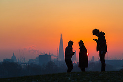 London, December 12 2017. Early morning walkers in silhouette against the city's skyline as the sun rises on a clear very cold morning in London, seen from Primrose Hill in Camden. © Paul Davey