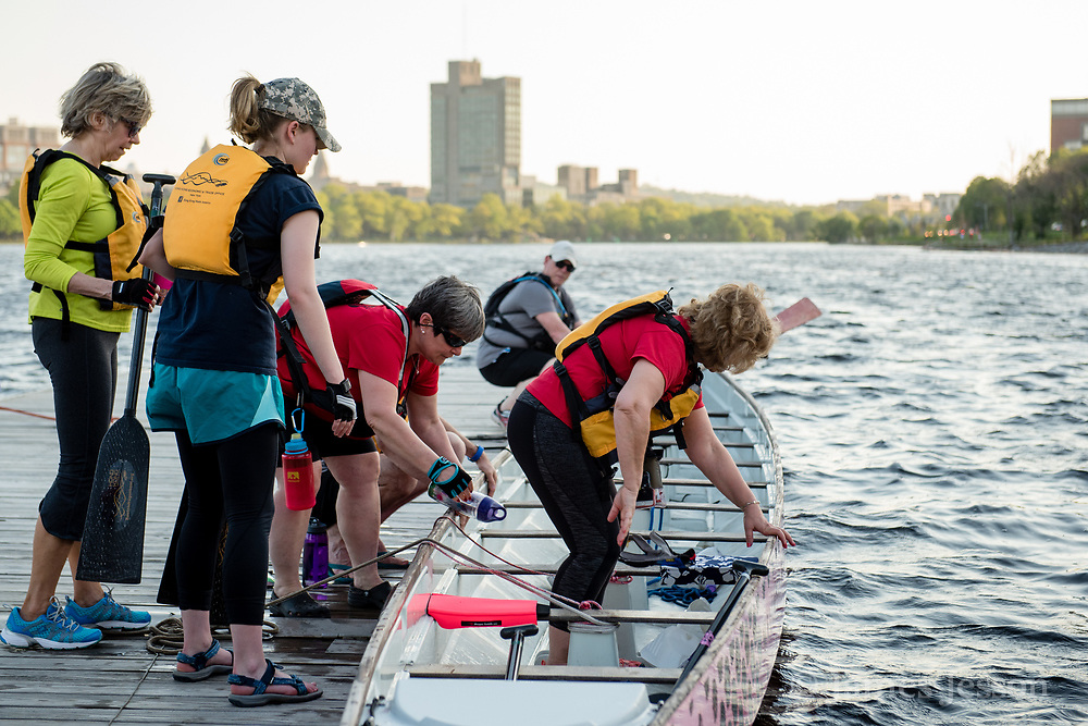 Wellness Warrior team paddlers load into their dragon boat one by one during practice on the Charles River near the MIT Pierce Boathouse in Cambridge, May 17, 2017.   [Wicked Local Photo/James Jesson]