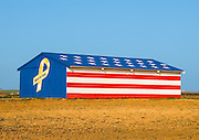 A Barn in an Open Field Painted in the American Flag with Support Our Troops