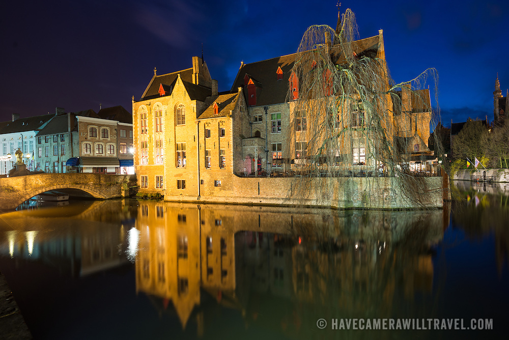 """Sometimes called """"The Venice of the North,"""" the historic Flemish city of Bruges has canals running through the old town. Before the water access became silted up, Bruges was a major commercial port. The building in the center of frame is the 15th century mayor's house, the Perez de Malvenda, where the Holy Blood was kept."""