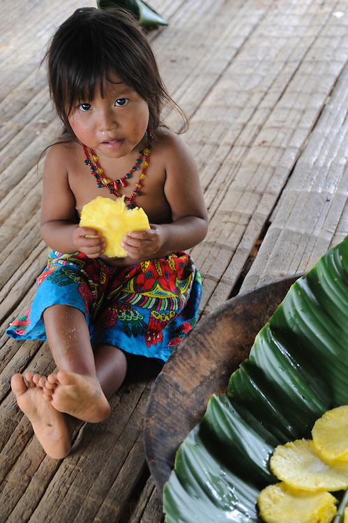 Indígenas emberá / comunidad indígena emberá, Panamá.<br /> <br /> Niña indígena comiendo piña.