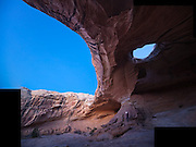 Leif Anderson stands at twilight below the central buttress of Wild Horse Window, San Rafael Swell, Utah.