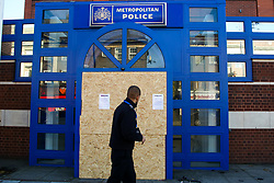 © Licensed to London News Pictures. 12/11/2020. London, UK. A police officer walks past the entrance to Edmonton Police Station in north London which is boarded up following an incident where a vehicle was driven into the police station just before 7pm on Wednesday, 11 November. A 45-year-old man left the vehicle before attempting to set fire to it using petrol. He was arrested by officers on suspicion of arson and is remanded in custody. The incident is not being treated as terror-related. Photo credit: Dinendra Haria/LNP