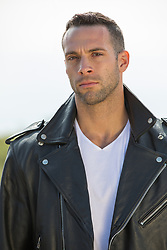 hot rugged man outdoors in a leather jacket