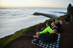 © Licensed to London News Pictures. 08/08/2020. City, UK. Walkers view the morning sunrise from the summit of Pen-y-Fan in the Brecon Beacons, on what is expected to be the hottest day of the year across the UK. The mountain which is the highest in southern Britain, has become increasingly popular with visitors who reach the top of the peak at first light to see the sun rising from the horizon. Photo credit: Robert Melen/LNP