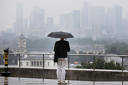 © Licensed to London News Pictures. 19/09/2021. London, UK. A woman shelters under umbrellas during a rain shower in Greenwich Park, South East London. A yellow weather warning for rain is in place for parts of England.  Photo credit: George Cracknell Wright/LNP