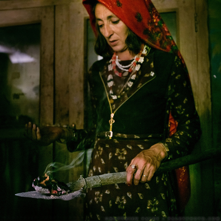 """The head woman of the household, named Samarkand, bless the house with burning """"Spandr"""", a local herb - a Pamiri tradition.  The festivities around the muslim celebration of Eid-e Qurban (the holiday of Sacrifice). The traditional life of the Wakhi people, in the Wakhan corridor, amongst the Pamir mountains."""