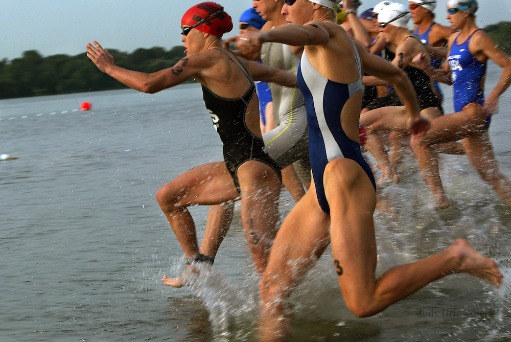 Women competitors sprint into the lake in Minneapolis, Minnesota at the start of a triathlon.