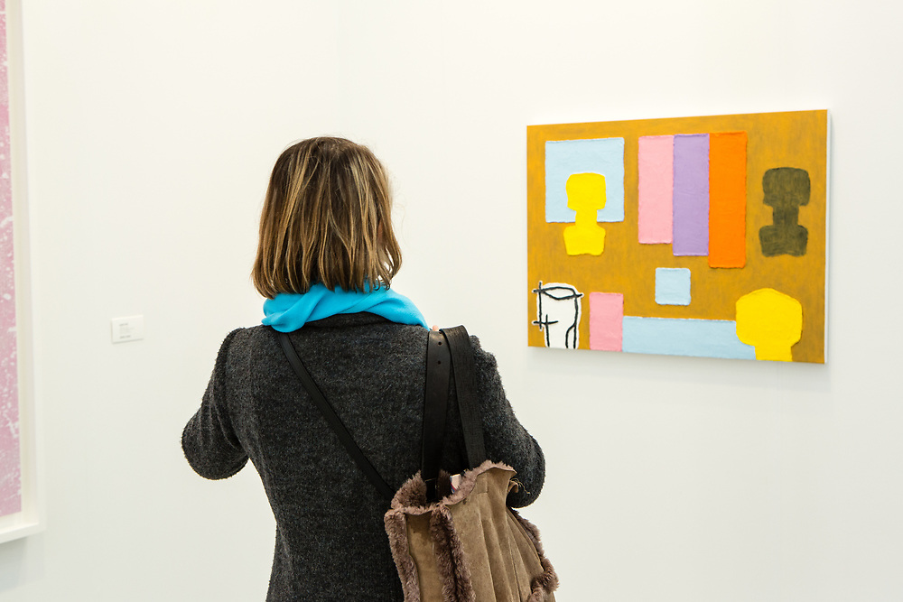 """New York, NY - 5 May 2017. The opening day of the Frieze Art Fair, showcasing modern and contemporary art presented by galleries from around the world, on Randall's Island in New York City. A woman looking at Jonathasn Lasker's oil on linen, """"To be titled,"""" 2017 at Cheim & Read."""